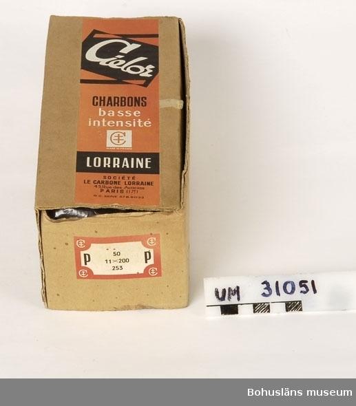 Förpackning med kolstavar, ursprungligen trol.  50 st,  i förpackning av papp märkt med svart och orange etikett med texten:  Cielor CHARBONS basse intensité LORRAINE SOCIETÉ LE CARBONE LORRAINE  På sidan oval svart etikett med röda texten: SVENSKA AB Le Carbone SUNDBYBERG HUVUD-DEPÔT FÖR LORRAINE KOL I SKANDINAVIEN  Båglampa, koncentrerad ljuskälla med mycket högt ljusflöde, där ljuset utsänds från en bågurladdning, en ljusbåge mellan två elektroder av grafit. I en sådan ljusbåge (kolbåge) kommer ljuset huvudsakligen från anoden, som kan ha temperaturen 3 500-6 000 °C. Genom förångning förbrukas elektroderna i kolbågen och måste efter hand matas fram. Denna nackdel är eliminerad i slutna båglampor, där urladdningen sker i xenon eller kvicksilverånga under högt tryck. Ljuset utsänds från området mellan elektroderna.    Har använts tillsammans med  projektor UM31031.   Projektorn är tillverkad av AEG på 1920-talet och har använts i Folkets Hus i Sjöbol vid Lysekil.  Till projektorn hör en lång rad delar och olika tillbehör, UM31031 - UM31062.  För ytterligare upplysningar om filmprojektorn, dess olika delar och användning, se UM31031.