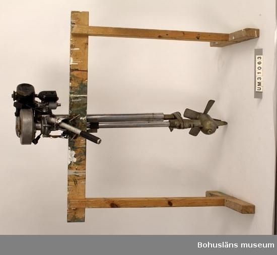 """Föremålet visas i basutställningen Kustland,  Bohusläns museum, Uddevalla.  Utombordsmotor av märket """"Seagull"""" av grå icke rostande metall (aluminium) upptill och koppardelar nertill. Överst rund platt cylinderformad del med utstickande """"lock"""", under den en gjuten motordel (med bl a ett tändstift), under motordelen ett fäste med två tvingskruvar att fästa motorn i båten med. Riggen består av två tjockare och två tunna kopparrör som ska sticka ner i vattnet. Allra längst ner en del med propeller av koppar fastskruvad nertill på rördelarna. Svartlackerad bensintank med """"SEAGULL"""" präglat på kortsidan. Ingjutet i relief på """"locket"""" överst står: """" The best Outdoor Motor for the World"""".   På motordelen en metalletikett med nummer och texten:  Märke: British Seagull. 2 Hk. Tillverkad 1962. Serienr. 40+ Motorn har lång rigg - för segelbåt - och är i väl fungerande skick"""