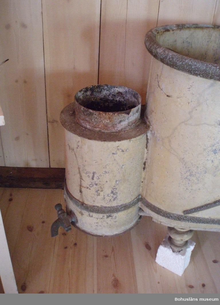 """Badkar från sekelskiftet 1900, Gåsö, Bohuslän. """"Nyckhålsformad"""" förzinkad plåt, gulmålat marmorerat, med omvikt kant och svarvade ben av trä, ca 180 cm långt.  Tvålkopp, tre avtappningshål varav två med korkar i. Två kryss stagar upp badkaret på respektive sidor. Karet är försett med uppvärmnings- (av järn) och avtappningsanordning (av mässing). Ett rökanslutnings-rör fattas. Badkaret liknar en empiresoffa till formen.  Korrosion och saltutfällning."""