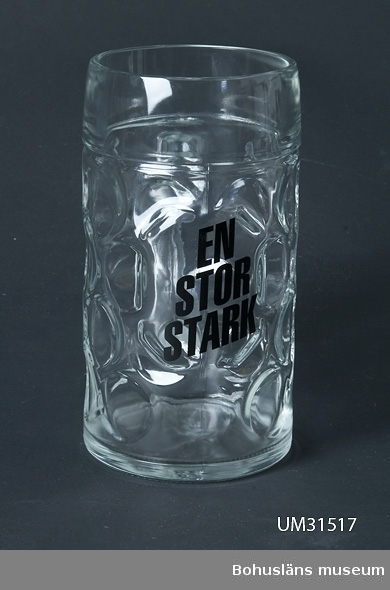"""Ölsejdel av klart tjockväggigt glas med ingjutna rundlar. Kraftigt handtag. På sidan tryckt text i spärrad stil i svart: """"EN  STOR  STARK Sejdeln visades i utställningen Vin, sprit och riktiga karlar på Bohusläns museum sommaren 2009."""