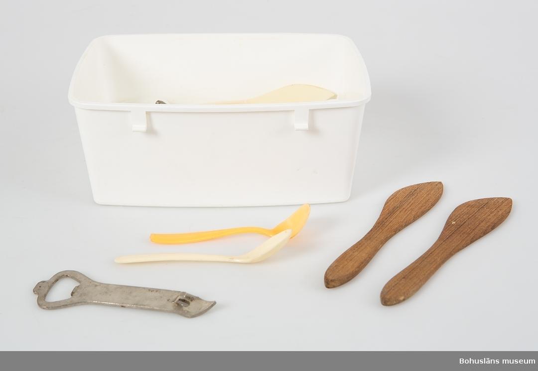 Rektangulär vit plastlåda med rosa plastlock. I lådan förvaras en samling engångsbestick av plast mest olika skedar, två smörknivar av teak, två äggkoppar av gul plast, en koservöppnare och ett plastlock. Konservöppnaren har instansade texten: MIRACLE CAN OPENER. Knäpplåsen för fästning runt locket saknas.