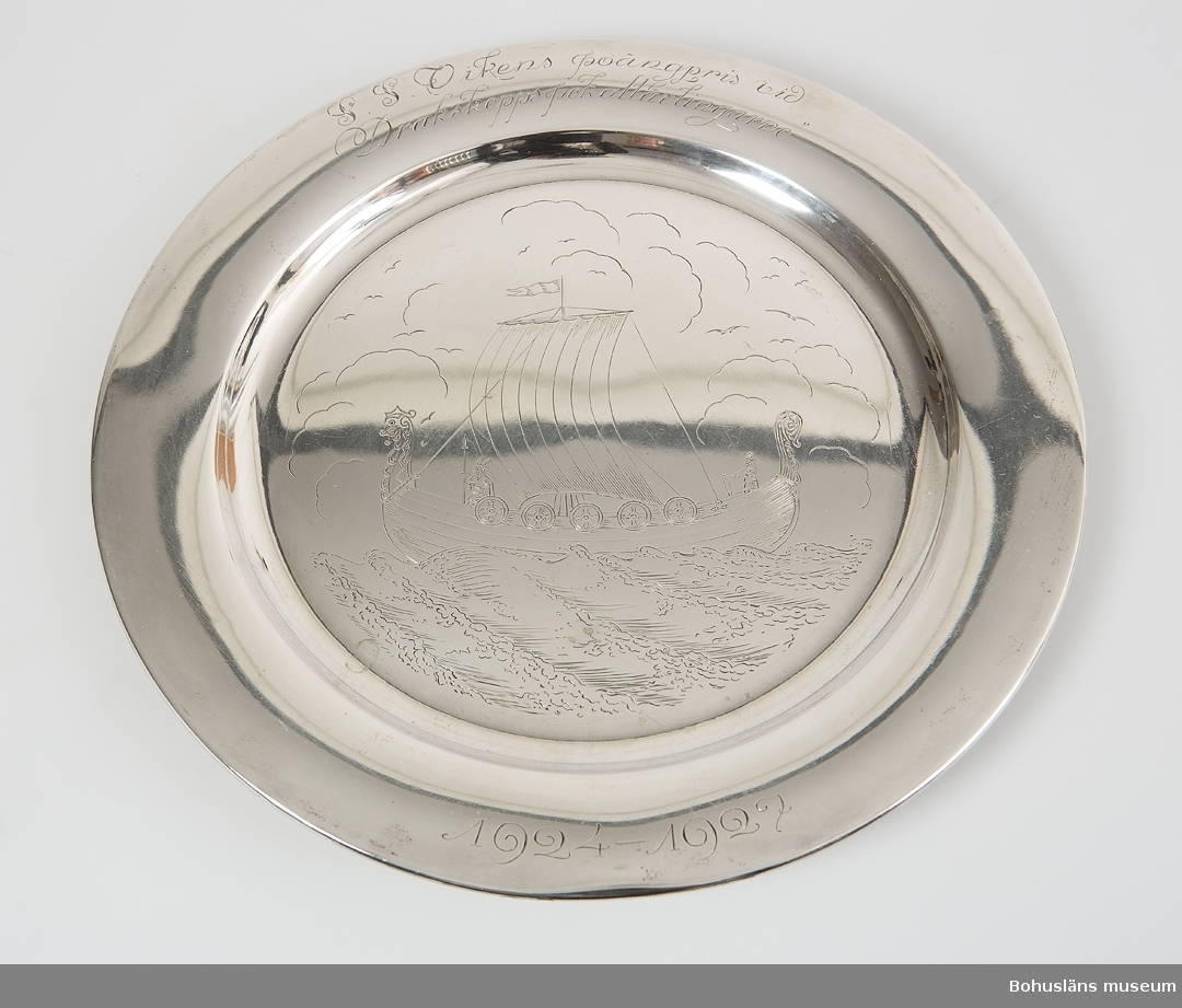 """Rund tallrik  av pressad silverplåt med svagt rundat bräm. På tallrikens spegel ett graverat vikingaskepp under segel,  på brämet graverade inskriften """"S. S. Vikens poängpris vid Drakskeppspokaltävlingarne"""" samt årtalen 1924 - 1927, jugendstil. På brämets baksidan stämplad med silversmed CCH; kattfot; S; Stockholms stadsstämpel samt årsbokstav V7 [1927]"""