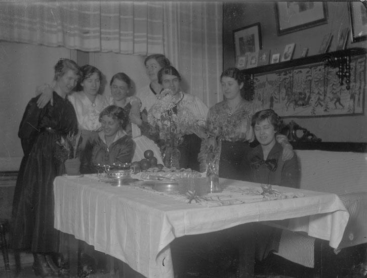 """Enl. text i blå bok: """"Grupp damer vid bord med blommor och kakor."""" ::"""