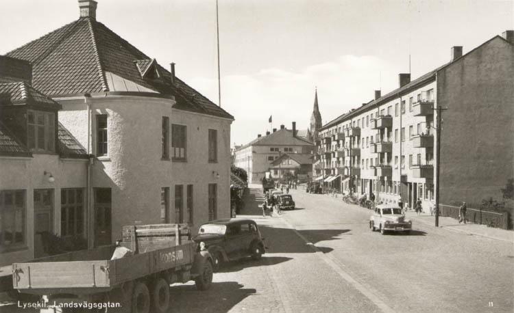 """Tryckt text på kortet: """"Lysekil. Landsvägsgatan."""" """"Förlag: Albert Wallins Bokhandel, Lysekil."""""""