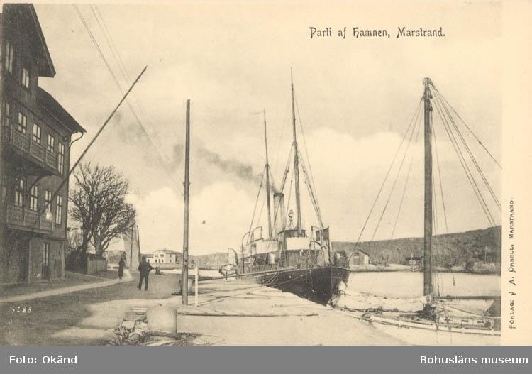 """Tryckt text på kortet: """"Parti af Hamnen, Marstrand."""" """"Förlag: J A. Qrsell."""""""