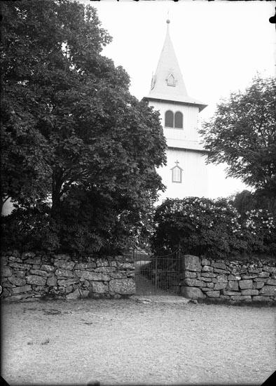 """Enligt fotografens anteckningar: """"Foss kyrka omkring 1900-talet. Den gamla grinden. Senare vit port""""."""