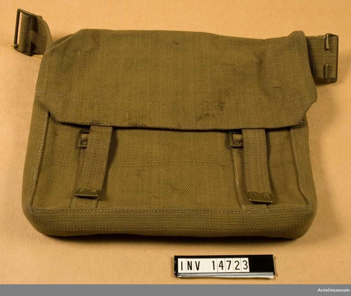 """Grupp C II. Brödväska (29 cm lång och 22 cm hög) av khakifärgat tjockt tyg (på engelska """"wibbing"""") och alla metalldelar (spännen, beslag) av mässing. Lock stänges med två remmar av samma tyg med spännen och beslag. På väskans båda sidor äro två spännen fastsydda, med vilka väskan sammankopplas med axelhänget. På lockets undersida finns en stämpel """"M.E.Co. 1918"""", och uppåtriktad pil """"156"""". På väskans baksida finns två korta remmar och spännen fastsydda."""