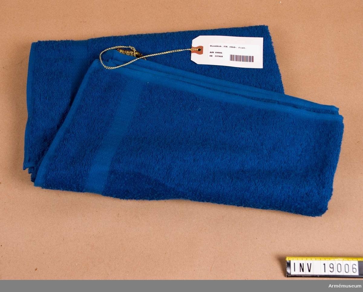 FN-förband. Av blå bomullsfrotté med ölgor på båda sidor och med hank på ena långsidan. Hanken är märkt: SOLSTA, 100 % bomull, tvättas separat första gångerna.
