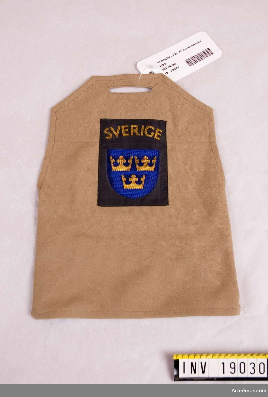 Ett beigefärgat underlag för nationsmärket Sverige över Tre kronor på blå sköld. Genom ett hål upptill träs axelklaffen och under ärmen sitter ett resårband som håller hylsan på plats. Bärs på vänster ärm till skjorta i utomlandstjänst. FN-tjänst. Tropikuniform.