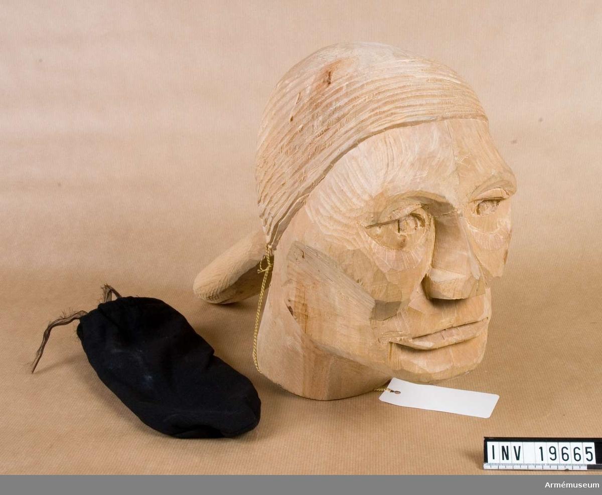 Trähuvudet föreställer en man med breda, grova drag. Håret (också skulpterat i trä) är samlat i en hårpung i nacken. Skulpturen är gjord av björkträ. På undersidan av halsen textat: Huggen 1975 av Gunnar Seger född 1921 (björk).   Samhörande nr AM AM.19664-5