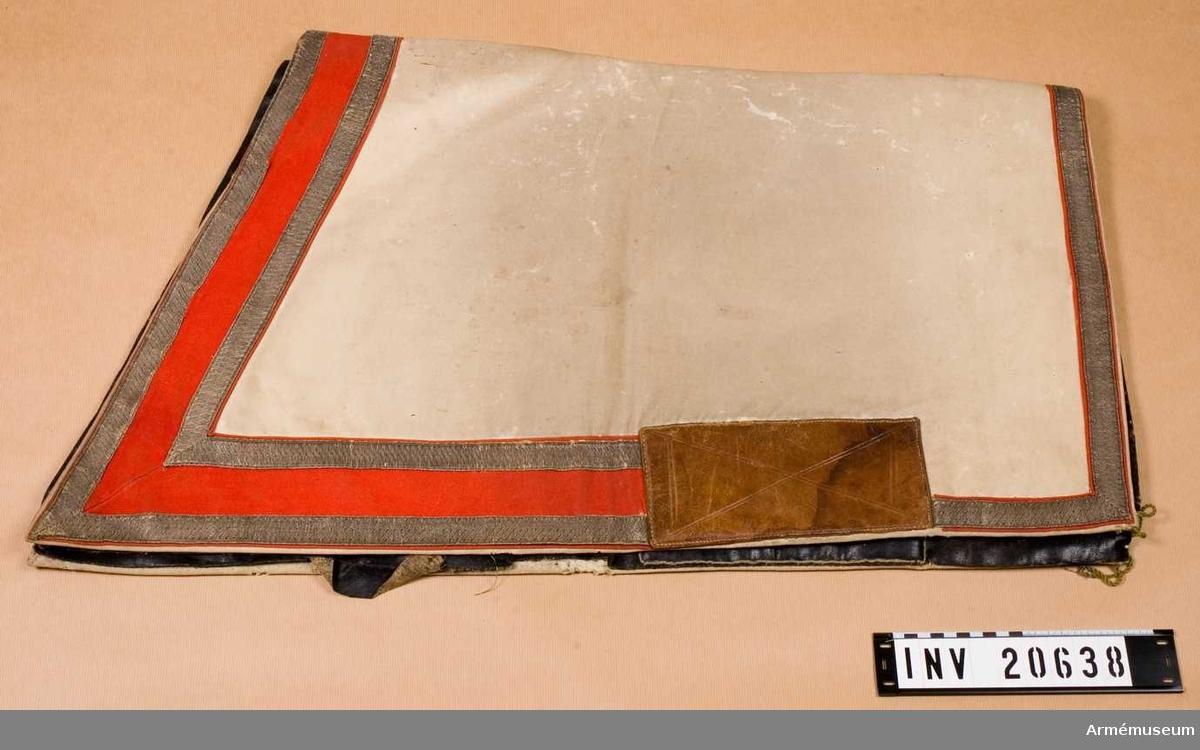 Grupp C I Schabrak av vitt kläde med fyrkantiga hörn. En remsa av rött kläde, b:90 mm, på ytterkanten och innanför. På remsans båda kanter fastsydd silvergalon, b:25 mm.  Foder av brunt vadmalstyg, grov lärft och svart, tjock vaxduk. I de främre hörnen finns knapphål av snören för at knäppa fast valtrappen vid sadel. På båda sidor fastsydda fyrkantiga läderbitar för att skydda valtrappen från slitning vid knäna.
