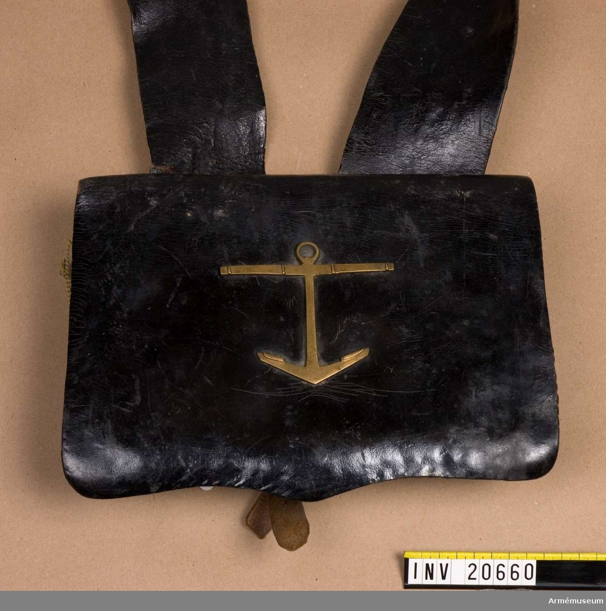 Av svart lackerat läder.  LOCK av tjockt, svart lackerat läder, fastsytt vid väskan. På locket ett ankare av mässing. Ankaret har på baksidan. en ögla med ett hål, varmed det fästes vid locket med hjälp av en  rem. För att locket skall behålla sin form finns på baksidan av locket en fastsydd läderbit.  VÄSKAN av grovt, svart lackerat läder. Ett tunnare läderlock betäcker väskan. På framsidan en liten läderficka med läderlock. På baksidan två korta remmar fastsydda vid sidorna. På nedre delen två fastsydda spännen. På högra sidan en ficka för bajonetten, som fästes med en rem. Väskan rymmer 30 patroner.
