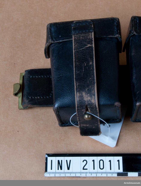 """Grupp C II. Patronväska för menig, cyckelordonnans, Tyskland. 1901. Av samma läder och med 3 patronknippen med 5 patroner i var. Patronerna för gevär m/1898. Varje väska stänges med remmar och knappar, på baksidan finns en rem för att fästa väskan vid livremmen med. På varje sida om livremsspännena fästes två väskor av vilka en har en ring för att sammankopplas med tornisternas axelrem. Pappersetikett med text """"Tyskland. Tillhör utrustningen för velocipedordonnanser. Bekommen år 1901, genom inköp""""."""