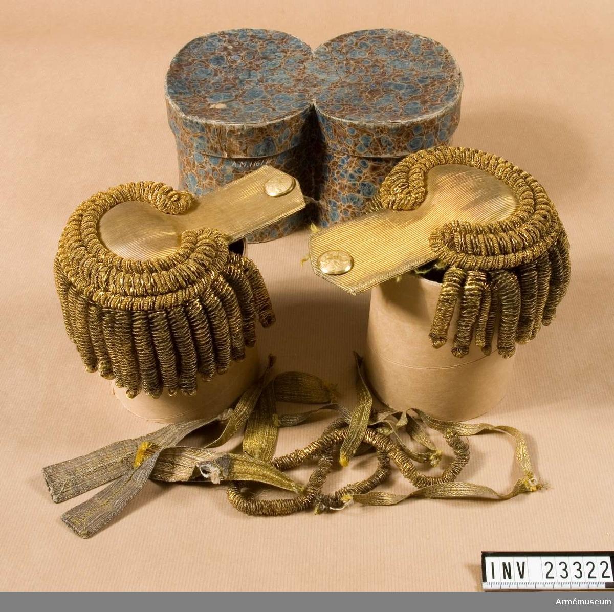 Grupp C. I guld med grova guldbuljoner. Knapp med Östgöta vapen. I asken ligger även guldgaloner och en lös guldbuljon. Buljonen kan ha suttit på en bicorn, medan fyra av galonerna ser ut som gradbeteckningar i form av knapphål som satt på kragen för kompaniofficerare i början av 1800-talet. 2016-11-02 MM.