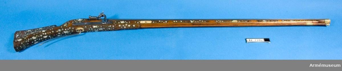 Grupp E II a. Musköt med luntlås, cirka 1600, av västeuropeisk typ.   Loppets relativa längd: 60 kaliber. Den åttkantiga, blanka pipan är längst bak litet fasonerad. Litet framför bakänden finnes ett 9,4 cm långt, fasonerat rörsikte och vid mynningen ett järnkorn. Fängpannan är fäst vid pipan. Fängpannelocket och eldskärmen är försvunna.  Pipan har två häften och en nedifrån insatt korsskruv. Luntlåset har hävstångsavtryckare, fjädern är förkommen. Låset fasthålles av två från höger insatta träskruvar med fyrkantiga huvuden. Varje huvud har två skåror, som korsa varandra.   Stocken är närmast av den fransk-engelska typen, av brunt trä samt prydd med inläggningar av graverat horn, pärlemor och mässingstråd, eller rättare sagt kantställda remsor av mässingsbleck.  Laddstaksrännan är öppen till större delen av sin längd och har rörka av mässingsplåt. Näsbeslaget är av hjorthorn, bakplåten är förkommen. Laddstocken är av brunt trä med huvud av hjorthorn.