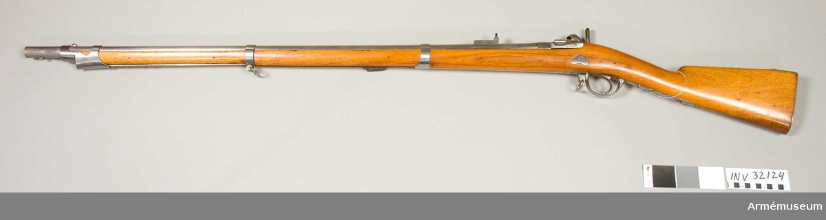 """Grupp E II.  Förändringsmodell 1868 från m/1857. Antal refflor 4 st Loppets rel längd 54,3 kal. Geväret är ursprungligen ett slätborrat gevär, som uppräfflats och ändrats enligt år 1857 faställd modell och som sedan ändrats till bakladdningsgevär, enligt 1868 fastställd modell. Bakladdningsmekanismen är av Sniders system, i Frankrike kallad """"a la tabatière"""".  Samhörande nr AM.032124-AM.032125, bakladdningsgevär, bajonett."""