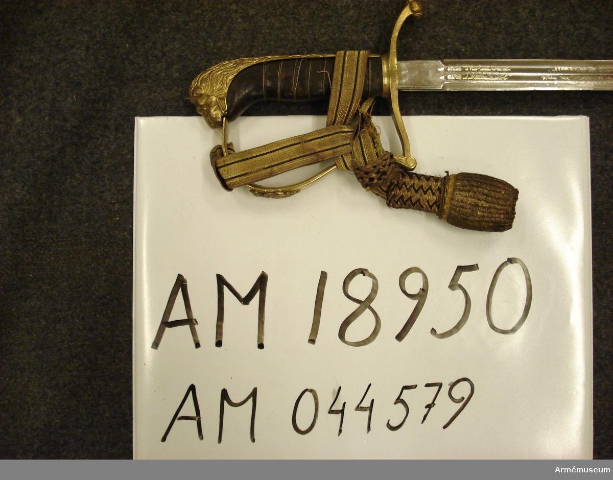 Samhörande nummer är 44577-79, sabel, balja, portepé. Grupp D II. Förvärvshistoria: Enligt inventarieförteckningen har föremålet burits av kapten H. Ahlgren. Kapten H. Broms gav år 1927 föremålet till Göta livgarde, som lämnade det till AM som deposition 1940-03-30. Från AM deponerades föremålet till P 1 1949-07-01. 1952-03-12 fick AM föremålet som gåva av Göta Livgardes kamratförening.Se även ink dnr.116, 13/3 1952.