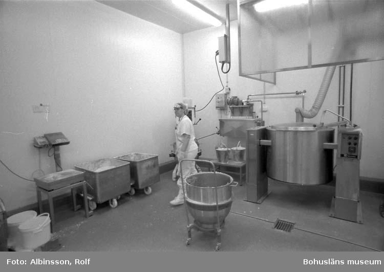 """Enligt fotografens noteringar: """"Såsrummet, till vänster vågen. Birgitta Andersson håller på med potatismoset."""" Fototid: 1996-01-19."""