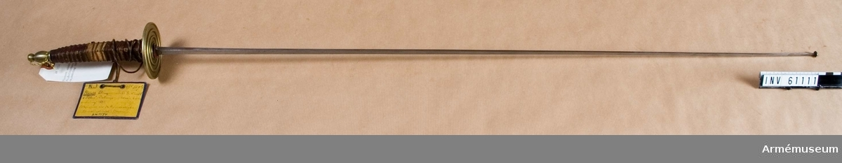 """Grupp D III. Klingans bredd är 10 mm och avsmalnande mot klingspetsen.  Den är märkt """"Fr. Neff & Söhne, Solingen"""". Parerplåten är av  mässing, räfflad och av en mindre modell. Kaveln är krökt och  omlindad med röd saffian."""