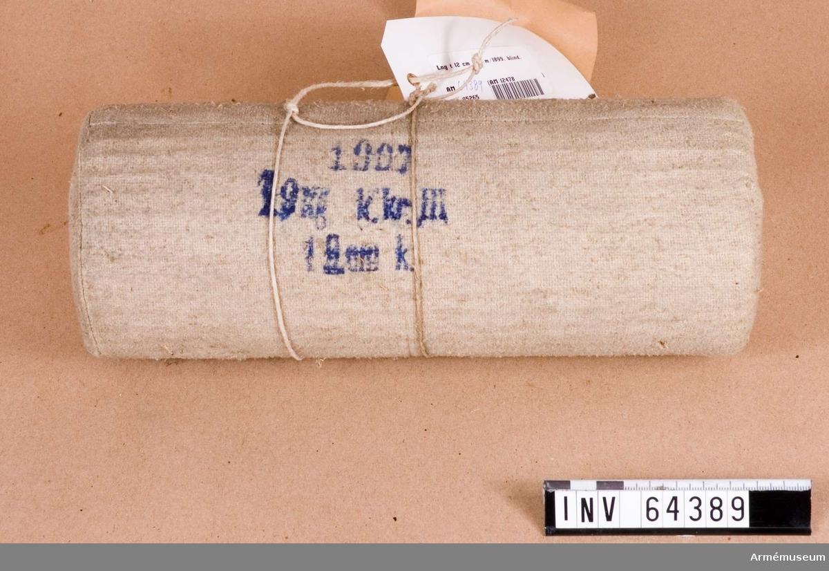 "Grupp F II.  Blind. Laddning av trä. Ytterhölje av grovt tyg märkt: ""1907, 1,9 kg. k kr. II, 12 cm k."""