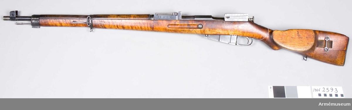 """Består av: 1 kikargevär, 1 gevärsrem av läder.Tillverkat 1944. Kaliber 7,62 mm. Pipan märkt """"(SA) (VKT) D. Stocken nr: 12."""