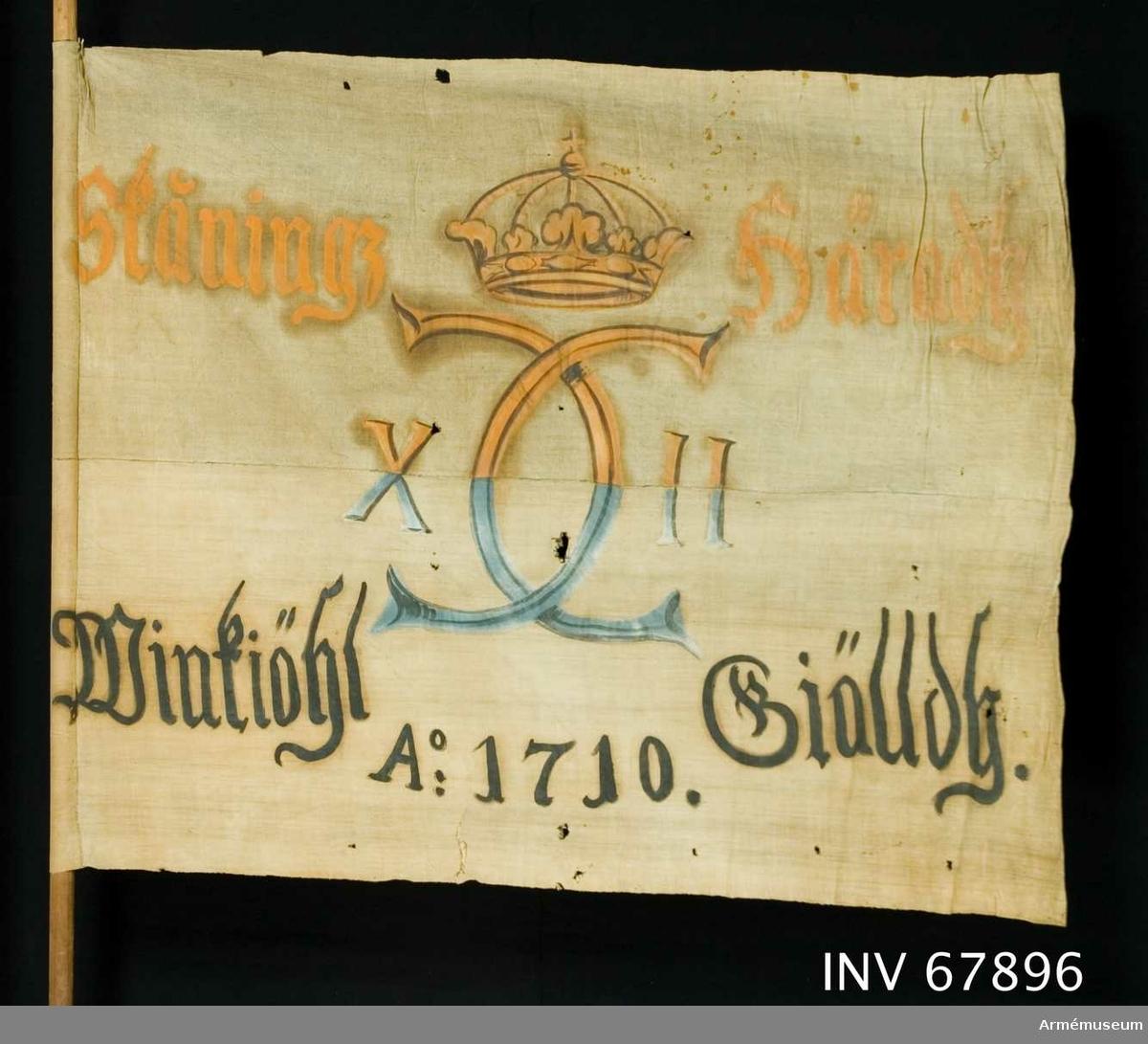 Duk: Tillverkad av enkel vit linnelärft, sydd av två horisontella våder.  Dekor: Målad endast från dukens insida. I mitten Karl XII:s namnchiffer, dubbelt C med X-II på ömse sidor, krönt med sluten krona i rött i det övre fältet, blått i det nedre. Text på ömse sidor om chiffret; upptill i gult med konturer i brunt och nedtill i svart.  Märkt: På stången påskrift av bläck(?). Rest av ett lacksigill.