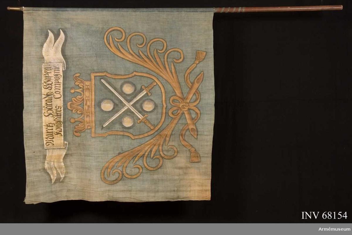 Duk: Tillverkad av enkel linnelärft. Vådkant i vertikala ytterkanten. Fäst vid stången med separat strumpa. Duken därpå fäst med en rad sexstjärniga tennlikor av mässing på blått band. Bandet fortsätter ned på stången.  Dekor: Målad lika på båda sidor i mitten i gult, en sköld krönt med öppen krona. Nedtill innefattad av två korsade palmkvistar hopknutna med långa tofsprydda band. I skölden två korsade svärd med vita klingor och gula fästen följda av fyra vita kulor i vinklarna. Över vapnet ett inspriptionsband i vitt med svart text.  Stång: Tillverkad av brunmålat trä. Holk av mässing.