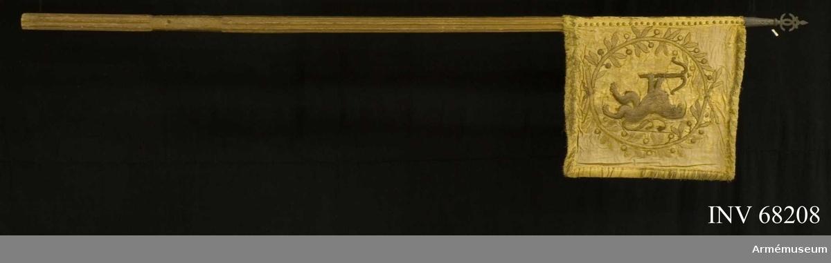 Duk: Tillverkad av dubbel gul sidendamast, mycket fragmentarisk; lagad med shantung, Pietas 1910. (Pietas nr 32). Duken fäst vid stången med tre rader tättsittande tennlickor på gula band.  Dekor:  Broderad i reliefbroderi, läggsöm, huvudsakligen på dukens insida - Smålands lejon förande ett spänt armborst i en helt omslutande lagerkrans nedtill och upptill hopbunden, allt i guld (metalltråd); på utsidan två palmkvistar hopbundna nedtill (har förmodligen inneslutit ett dubbelt C); i inre, övre hörnet rester av en 6:a(?), i inre, nedre hörnet en 4:a.  Frans: Dubbel, av gult silke och metalltråd.  Stång: Tillverkad av trä, kannelerad, gulbrunmålad och avsågad nedtill; saknar ring och löparten; holk och spets av järn (defekt!).