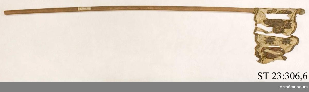 Duk av vit sidentaft och strumpa av rött linne försedd med frans vid öppningarna. Motivet målat i guld- och silver samt rött och grönt bestående av en krönt örn, måne, sol och stjärnor, På duken en pappersetikett som anger att den tagits i slaget vid Saladen 1703.
