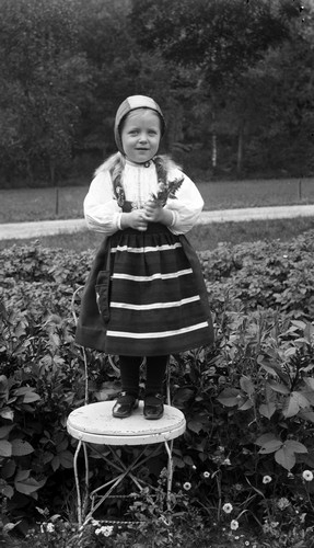 Flicka i bygdedräkt avporträtterad på en stol i en trädgård