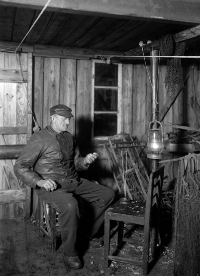 """Jan 1924. Fiskare med """"känseleg""""i sjöbod."""