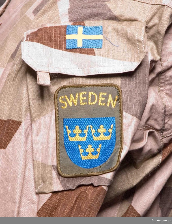 Utförd i ökenkamouflage. På vänster ärm: Förbandstecken (Utlandsstyrkan) och Nationalitetsmärke. Tillverkad 2007 i Kina.