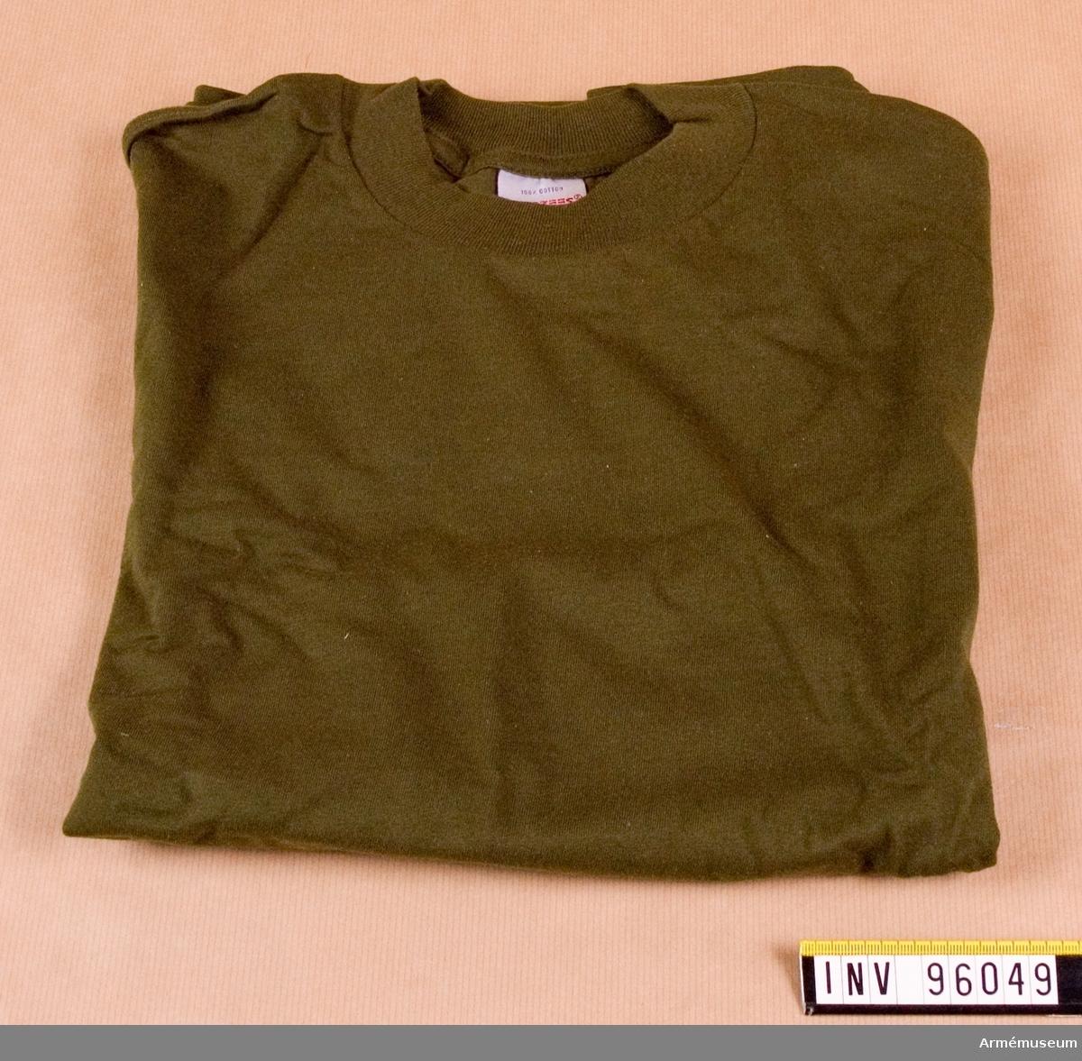 """Kortärmad, grön, t-shirt, stickad av 100% ringspunnen bomull. Tröjan är tillverkad i singeljersey med halsmudd i 1:1 ribb. Tröjan låg förpackad tillsammans med ytterligare 5 i en polyetenpåse med etikett: """"Arbetsmodell, T-shirt grön, M7321-161000-4, Eva Berglund, FMV:IntT 1995-04-11""""."""