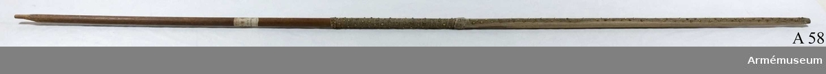 """Stång av furu. Rester av fanduk av vitt siden runt stångens övre del. Ca 150 förgyllda tännlikor fastspikade. Etikett från Riddarholmskyrkan: """"No 58 A""""."""