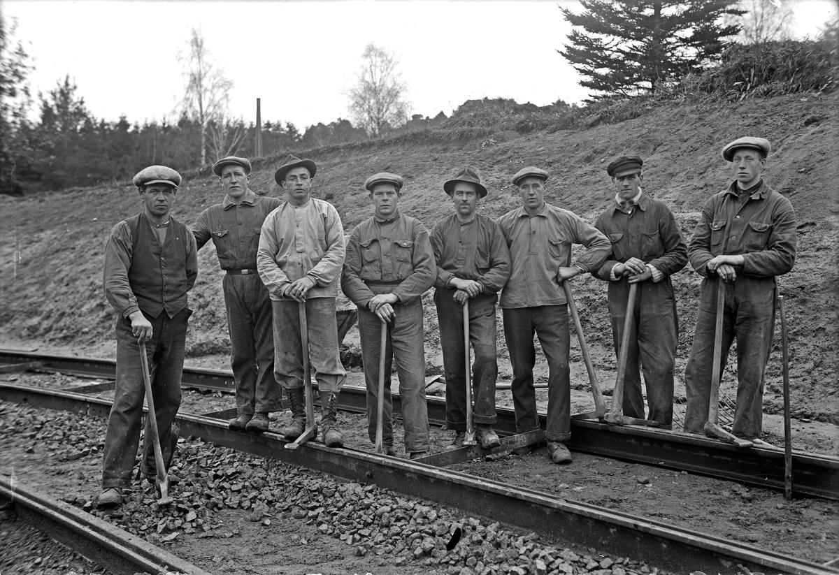 En grupp arbetare med hacka eller korp i handen. Troligen är det spårväg som anläggs genom Stadsparken norr om Stadsparksvallen i Jönköping.
