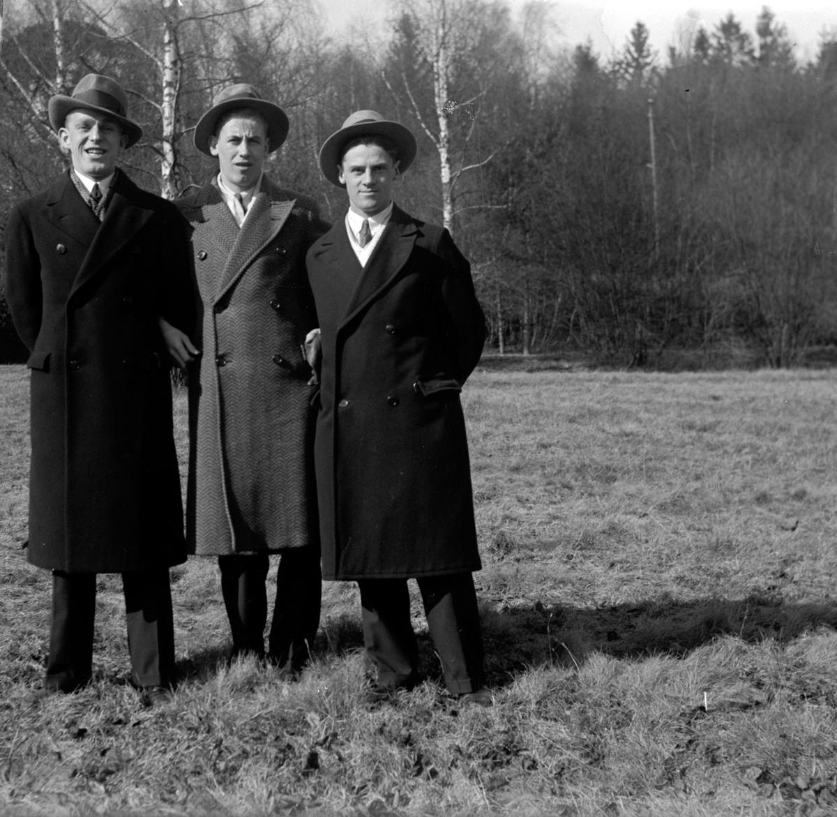 Tre män klädda i rock och hatt, står på ett fält med avlövade träd i bakgrunden.