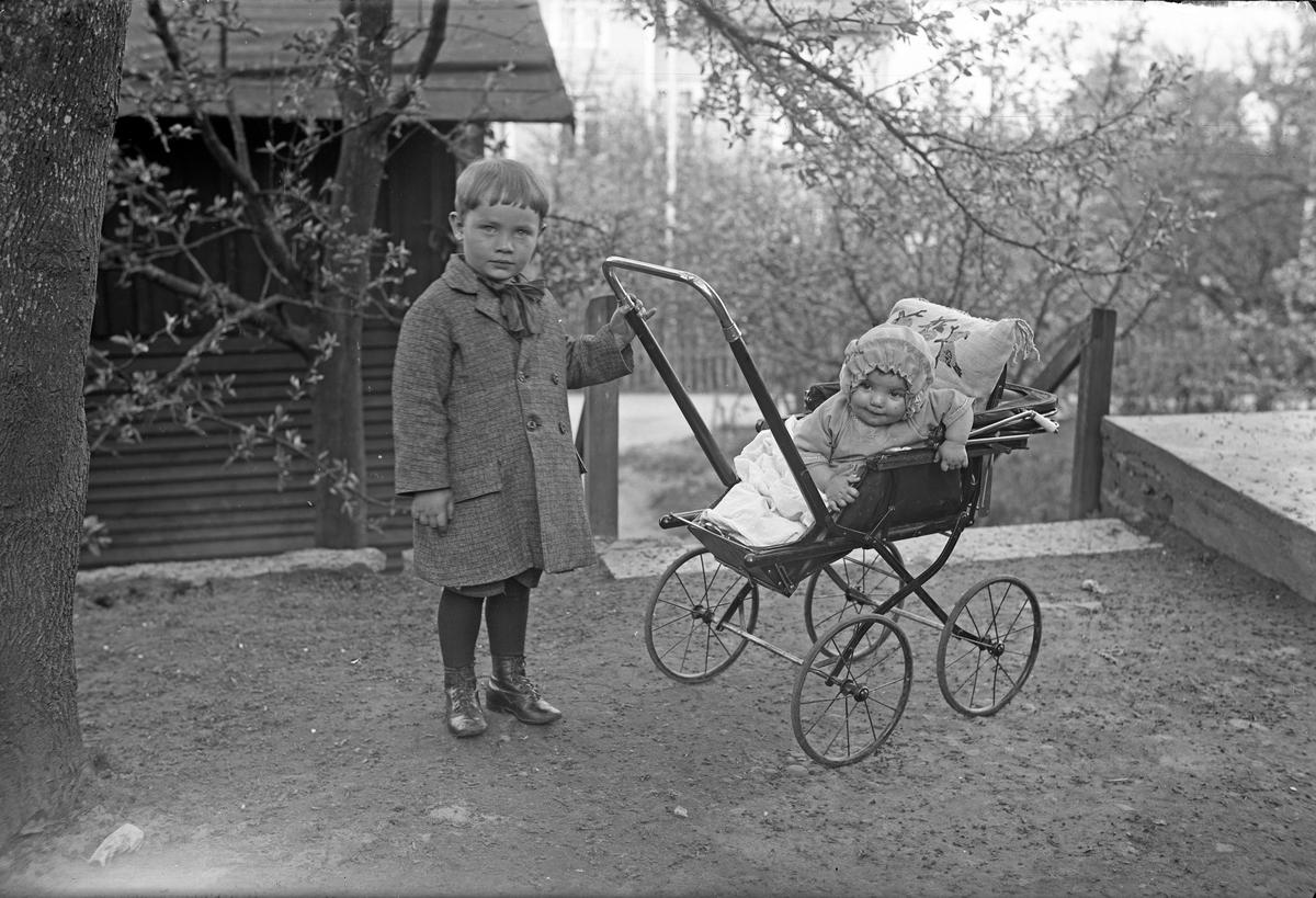 En liten pojke med ett barn i en barnvagn i Jönköping.