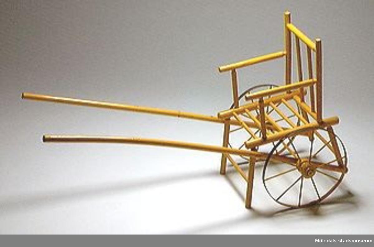 Dockkärra i form av stol på två hjul. Två skaklar att dra i. Den ena skakeln förstärkt med järnrör. Sekundärt gulmålad. Hjul av järn.Ett ben är av.Brukaren är gift Johansson (fru till givaren).