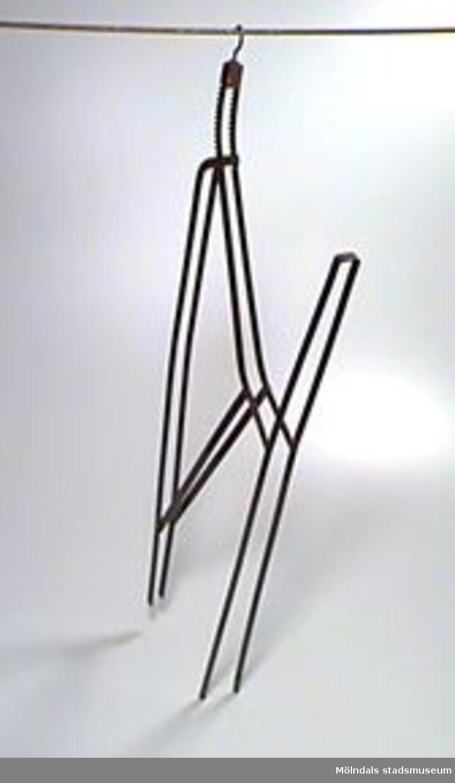 Byxspännare för två byxben. För skrädderiarbete med och pressning av byxor.Byxspännaren spänner ut byxbenen.Konstruktionen är parallellgjord. Inställbar bredd och tre rörliga nitade delar.Spännriktningen är 30 cm. Bredden ihopfälld: 100 mm.Färgen delvis bortnött. Rostig.Har tillhört givarens far.