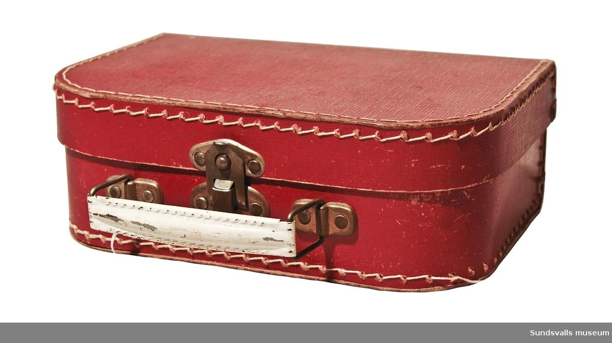 Röd frisörväska av papp som ihopfogats med hjälp av metallnitar och tråd. Handtag och låsanordning av metall. Handtaget är vitmålat. Användes av givarens far, Hjalmar Pettersson, som levde mellan 1896-1978.