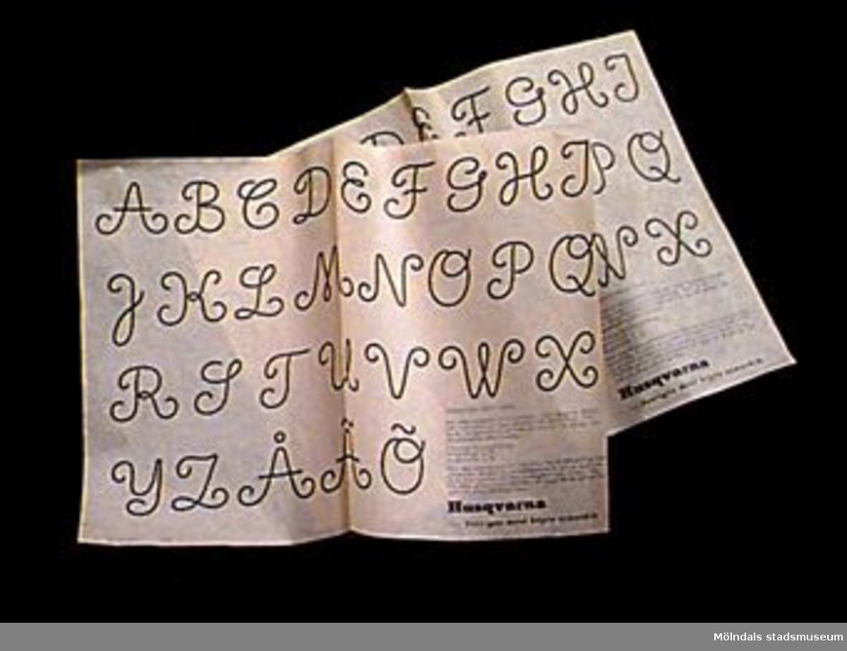 Alfabetet med ca 4 cm höga bokstäver. Ark med mallar för märkning med garn på symaskin och anvisningar. Samhör med övrigt material rörande linneförråd, 02706-02722, 02727-02729.Övriga uppgifter se 02643:1.