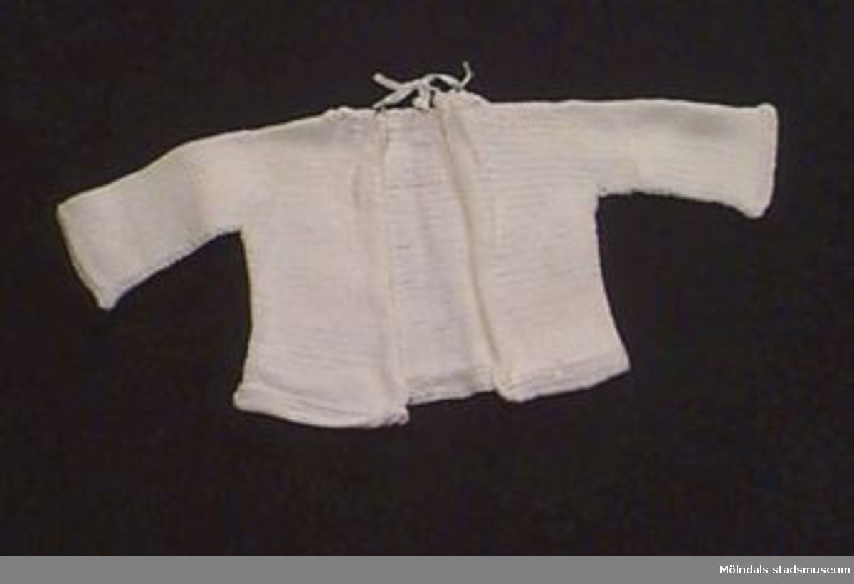 En vit stickad babykofta med öppet ryggparti. Knytning i nacken.
