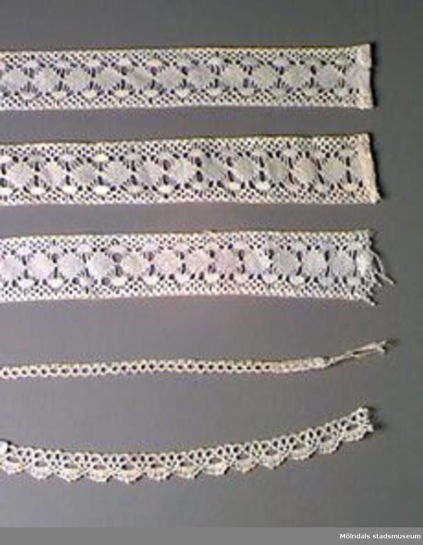 """Knypplade spetsar. MM02827:3 är vit, de övriga något beigeaktiga. MM02827:1 Spets utan uddar. L 640 mm, B 29 mm. Fållad i ena änden.:2 Spets utan uddar. Samma mönster som :1. L 600 mm, B 30 mm. Fållad i ena änden.:3 Spets utan uddar. Samma mönster som :1 och :2. L 615 mm, B 30 mm. Ofållad.:4 Smal spets med uddar. Mönstret finns i boken """"Knyppling"""" (MM02826) på sidan 24-25, övningsspets nr 2. L 390 mm, B 5 mm. Garnändarna är ihopknutna i ena änden av spetsen.:5 Spets med uttalat uddmönster. L 200 mm, B 12 mm. Gunvor Otter (f. 1916-12-21), ursprungligen från Gävle, flyttade till Toltorpsdalen (Fotbollsgatan 17) 1959. Till Bifrost flyttade hon 1991. Gunvor Otter är f.d. gymnasielärare i historia och svenska. 1955-1971 ca arbetade hon på Flickläroverket, därefter på Hvitfeldtska fram till pensioneringen 1981."""