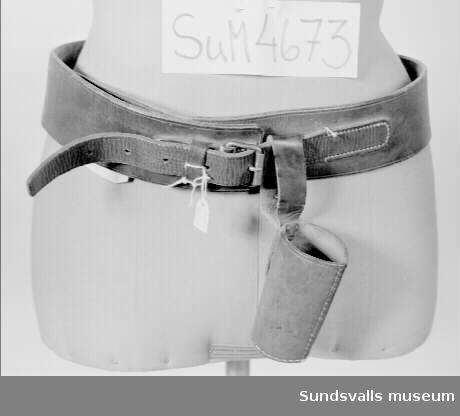 Bärbälte i brunt läder och metallspänne. En läderkorg med platt botten för fanstång är fasthängd på bältetmed en ögla i läder.
