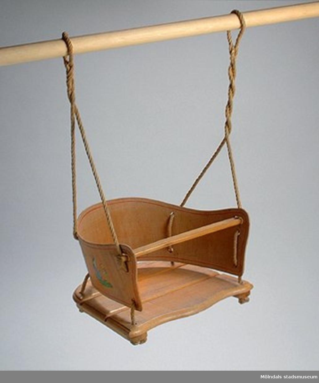Gunga i trä, med dekoration på sidorna. Använd på Skol- och vårdhemmet Stretered.