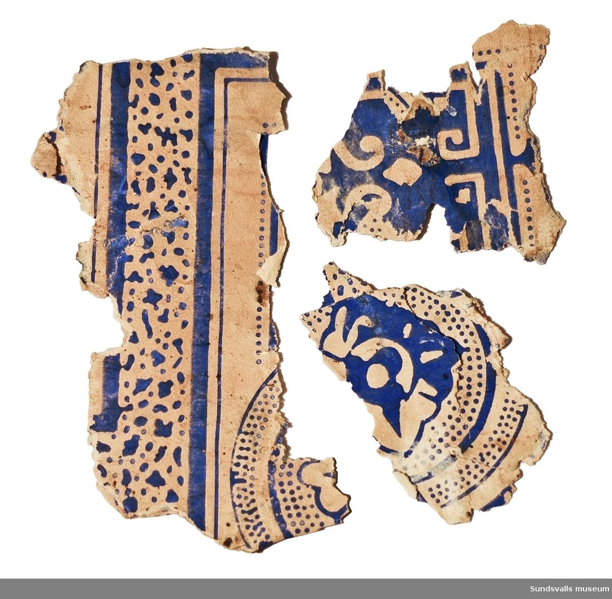 Fyra fragment av tapet med blått tryck som enligt uppgift är taget från sågverksarbetarbostaden i Nacka på norra Alnö. Fragmenten är hämtade från det understa tapetlagret i övre rummet, 5:an.