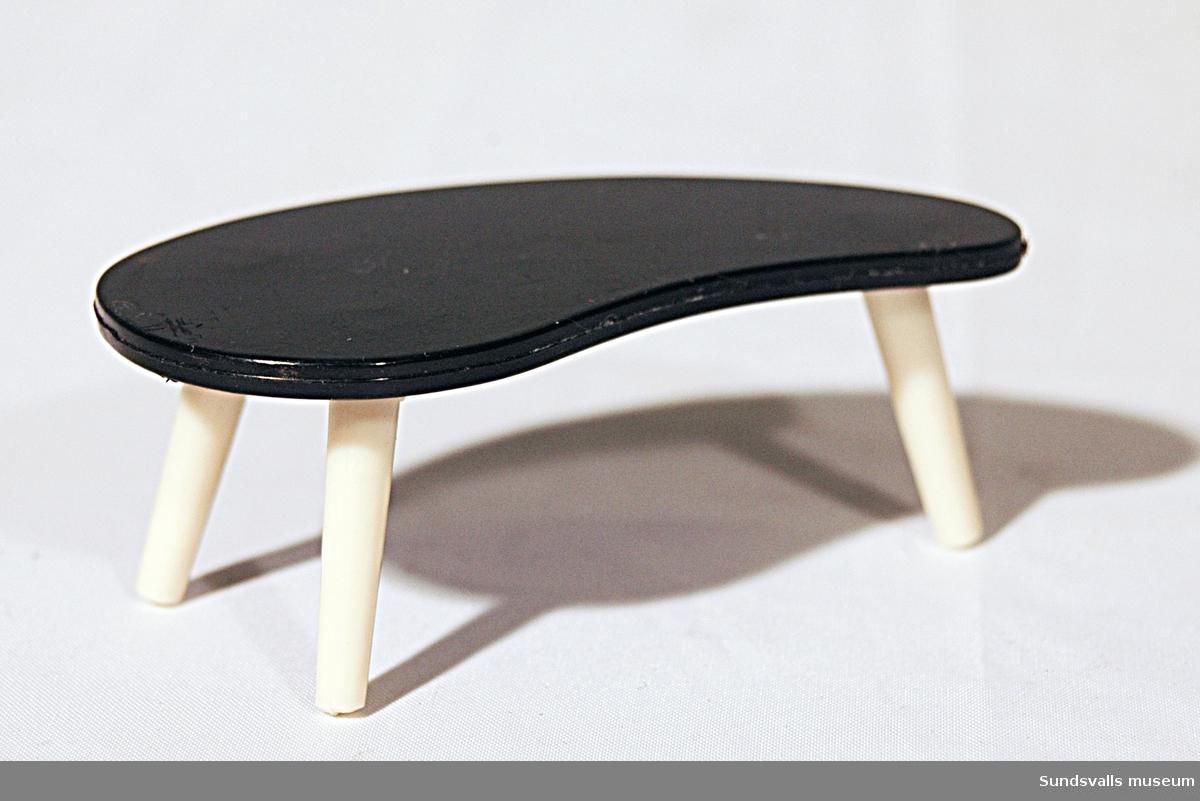 Dockskåpsmöbel. Njurformat bord med svart bordsskiva och vita ben. Plast.