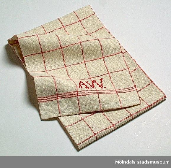 Kökshandduk, naturvit med rött rutmönster. Broderat kors- stygnsmonogram A.W i rött garn.