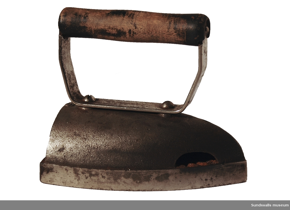 Strykjärn av metall med med svartmålat handtag i trä.