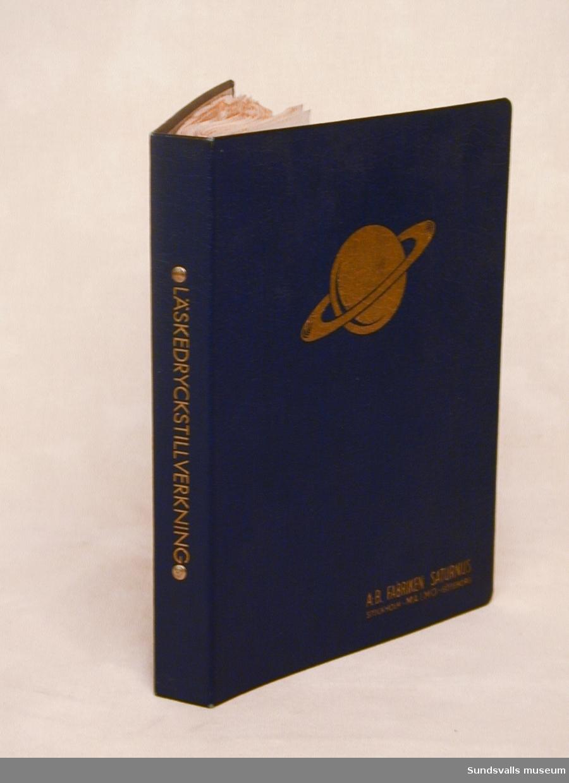 En mörkblå pärm med guldtext som det står A-B Fabriken SATURNUS, STOCKHOLM. MALMÖ. GÖTEBORG inhh. Mitt på pärmen en guld saturnus. Med 79 st. blad med recept, etiketter och bruksanvisning. På sidan av pärmen står det med guld: Läskedryckstillverkning.